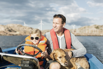 Girl driving motorboat with father and dog in Baltic Sea