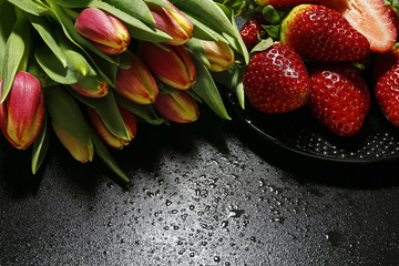 tulips and strawberries with water drops on black background