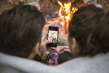 High angle view of couple taking selfie in mobile phone by fire pit at campsite