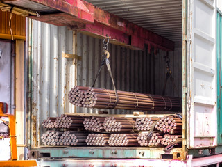 Unstuffing of steel round bar - iron metal rail lines material from container to store in warehouse.