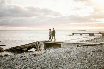Couple walking on jetty at beach against sky during sunset