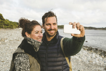 Happy couple taking selfie at beach against sky during sunset