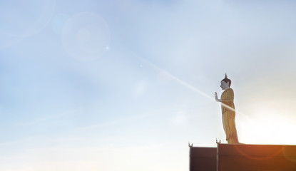Buddha image on roof top and wide sky with sunlight