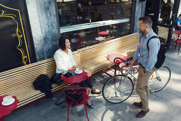 Businessman with bicycle talking to female colleague sitting at sidewalk cafe