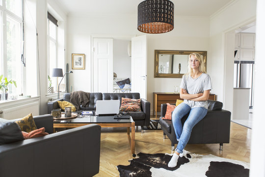 Full length of teenage girl sitting on sofa in living room at home