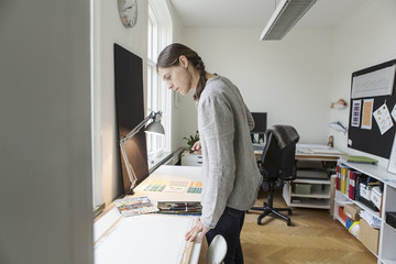 Serious woman looking at canvas while standing in creative office