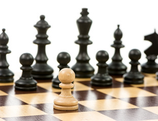 White pawn against a superiority of black chess pieces