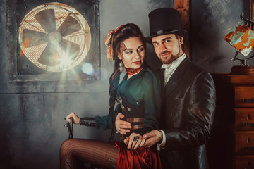 Pretty flirting couple dressed in vintage costumes on the dark room background.