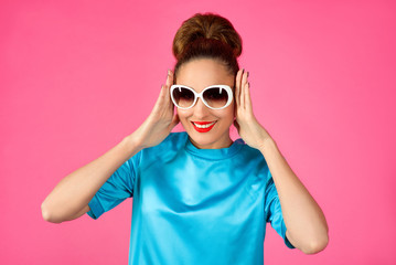 portrait of shocked and surprized young beautiful woman in blue silk dress and white sunglasses ot the pink background