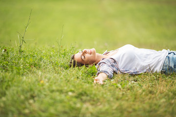 Young woman lying down on grass.She enjoys in the moment of peace.