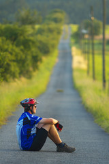 A cyclotourist sitting on the road