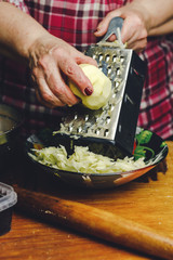 woman's hand grating apple in plate on kitchen.