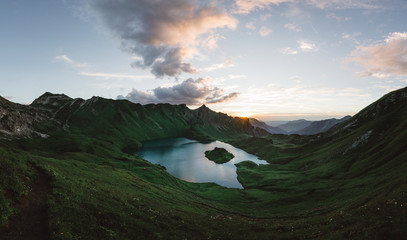 Lake surrounded by mountains against sky during sunset