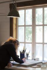 Female artist painting by a window in art studio