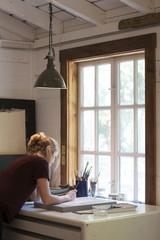 Female artist painting in light filled studio