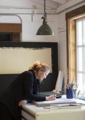 Female artist painting in light filled art studio