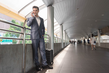 Business man with travel bag use smart phone on the walk way wit