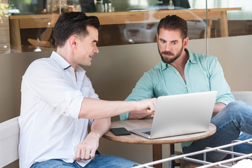 Two Westerner Business men working with laptop and smartphone to