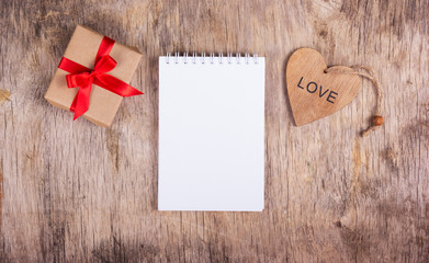 Notepad with blank pages and a surprise valentine wood.Notepad with blank pages and a surprise valentine wood. Copy space. Valentine's Day.