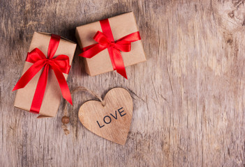 Two small boxes with a red bow and Valentine on the old wooden background. Copy space. Valentine's Day.