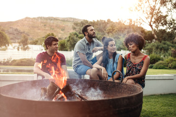 Young couples sitting near campfire at backyard