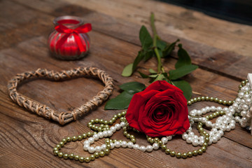 Dating in vintage style, red rose on wooden background with heart shaped, candle and bead. Present on Valentine's day, original congratulation.