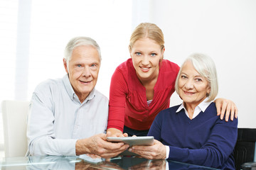 Senior couple using social network on tablet computer