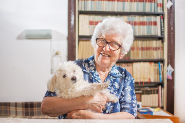 Happy old woman holding Maltese dog at home.