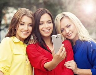 Gorgeous young women smiling and posing to take a selfie.