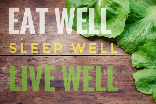 Eat well sleep well live well words on old wooden background with fresh green lettuce