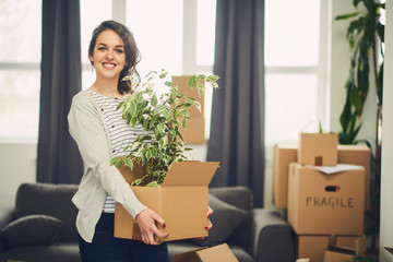 Woman with stuff for moving, in new apartment