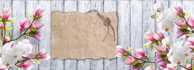 Magnolia with orchid and old paper on background of shabby woode