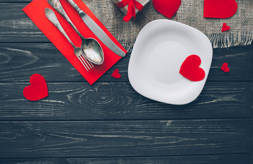Valentine's Day. red felt heart ,plate,cutlery,presents and decor on wooden background