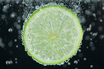 Lime slice falling into water