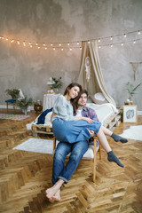 Young hipster couple having fun on old armchair with dreamcatche