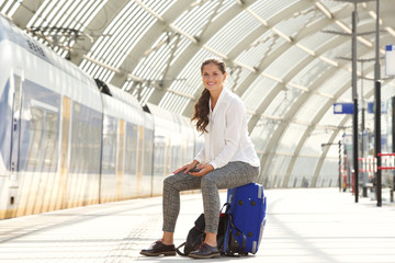 happy woman sitting on suitcase holding smart phone