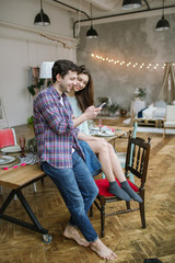 Young beautiful happy hipster couple with smartphone in rustic l