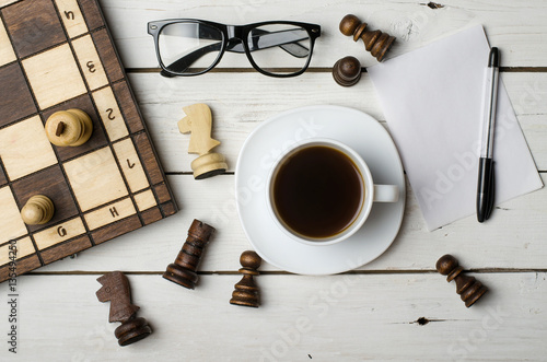 A Cup Of Hot Coffee And Chess Pieces On A Wooden Table
