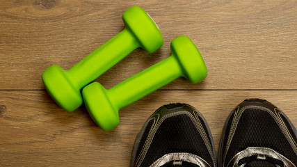 fitness lifestyles concept, dumbbells, sport shoes on wood background top view