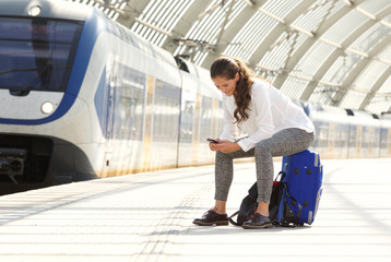 happy woman sitting on suitcase using mobile phone