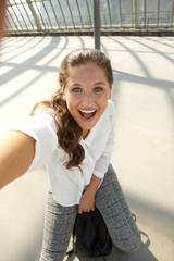 young woman sitting on suitcase taking herself photo