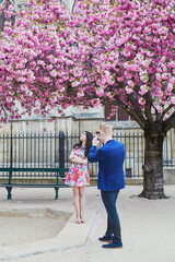 Romantic couple in Paris with cherry blossom trees