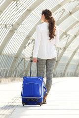 business woman walking at train station with suitcase