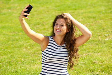happy young woman taking selfie outside