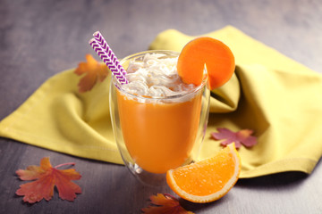 Glass of fresh pumpkin smoothie and napkin on table