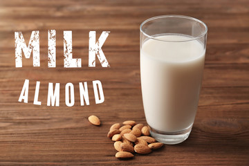 Food substitute concept. Glass with almond milk on wooden background