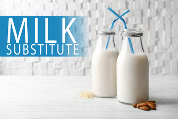 Food substitute concept. Glass bottles with different milk on white wooden background