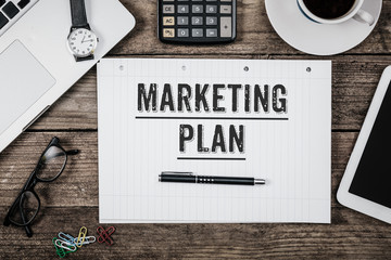 Marketing Plan text on note pad, Office desk with computer techn