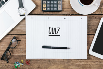 Quiz text on note pad, Office desk with computer technology, hig