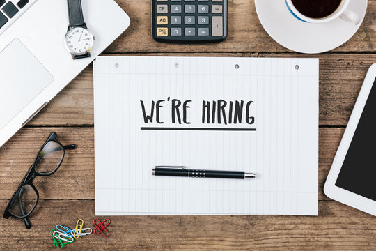 We Are Hiring text on note pad, Office desk with computer techno